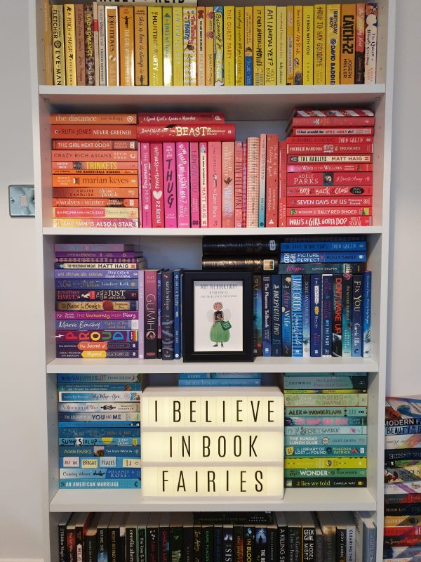 the book fairy print has been framed and added to a beautiful rainbow themed bookshelf