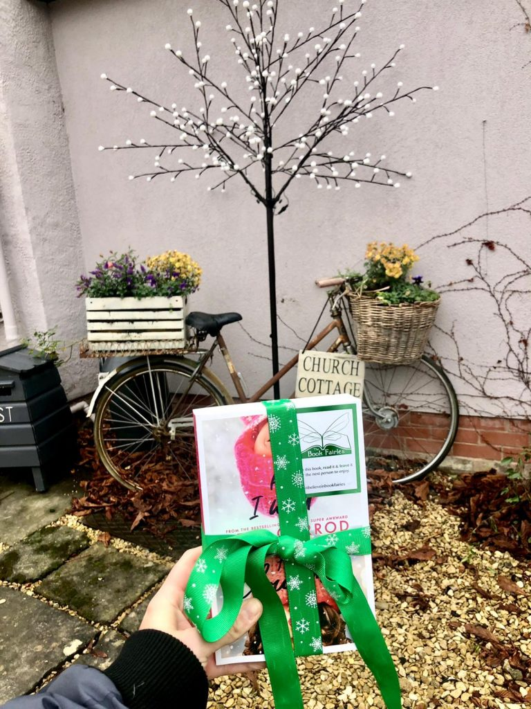 Hiding at a decorated bicycle - the book fairies hid copies of All I Want for Christmas by Beth Garrod