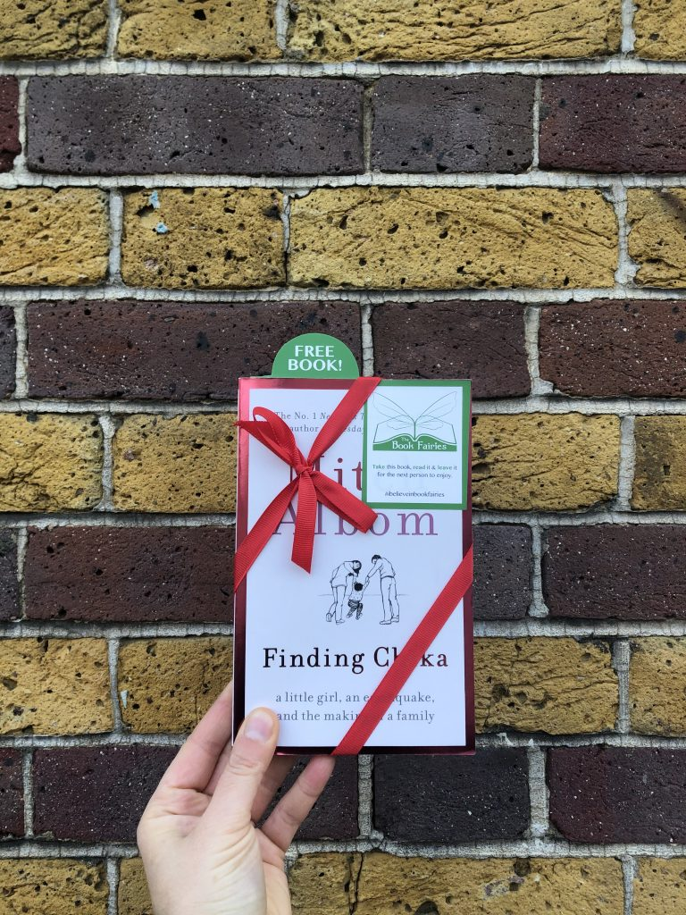Hiding outside a library - Book fairies hide copies of Mitch Albom novel Finding Chika