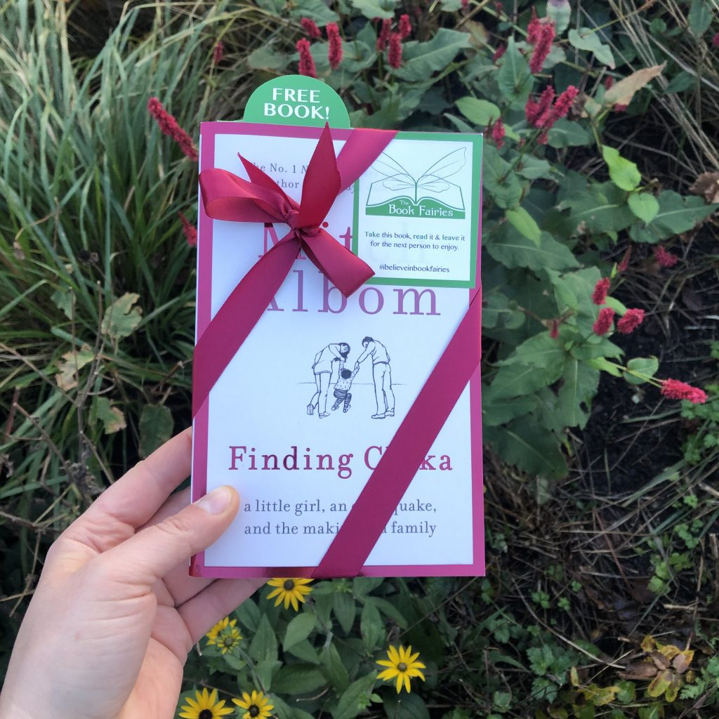 Near flowers - Book fairies hide copies of Mitch Albom novel Finding Chika