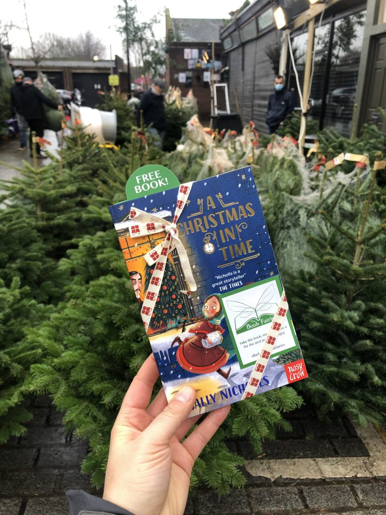 Hiding at a christmas tree market - The Book Fairies hide copies of A Christmas in Time with Nosy Crow Publishing
