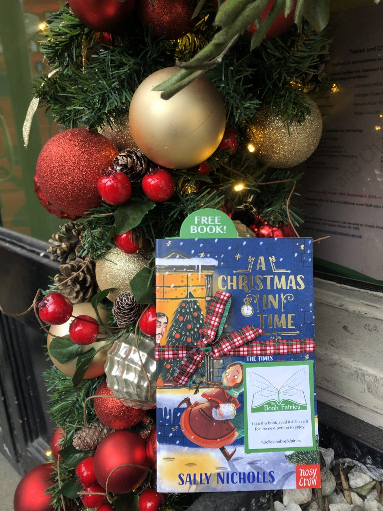 hiding at a festive display - The Book Fairies hide copies of A Christmas in Time with Nosy Crow Publishing