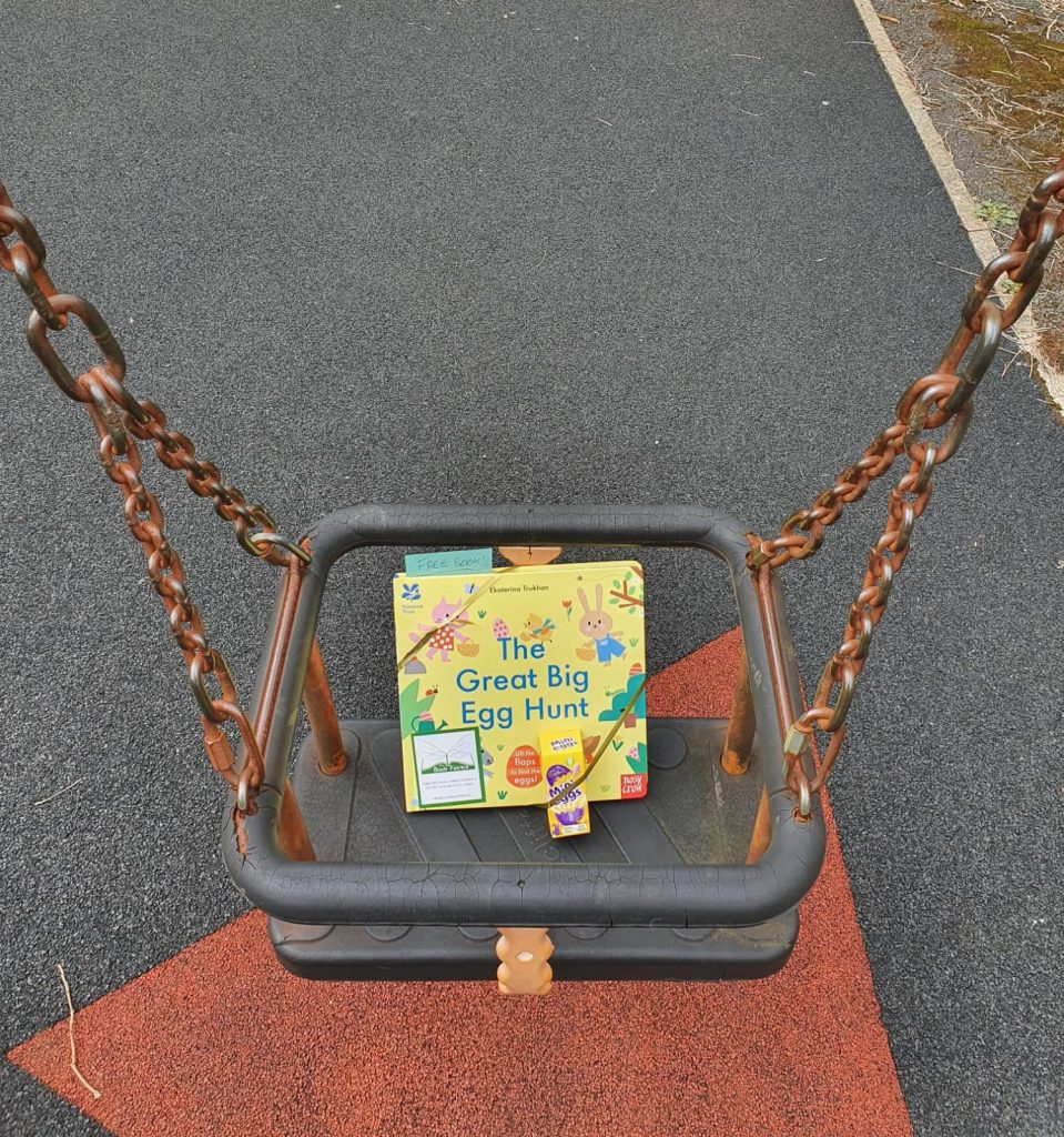 Hiding in a swing at a playground - Book fairies hide copies of National Trust title 'The Great Big Easter Hunt'
