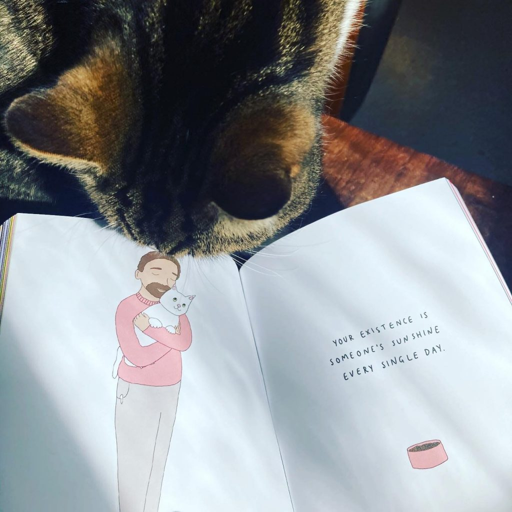 Cat and a book - Book Fairies hide copies of All Of This Is For You by Ruby Jones
