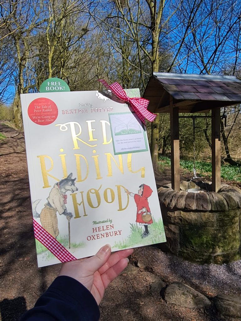 Hiding by a well - Book Fairies hide copies of Red Riding Hood by Beatrix Potter and Helen Oxenbury