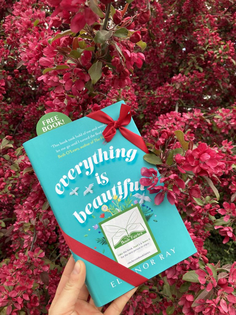 With flowers - Book Fairies hide copies of Everything is Beautiful by Eleanor Ray