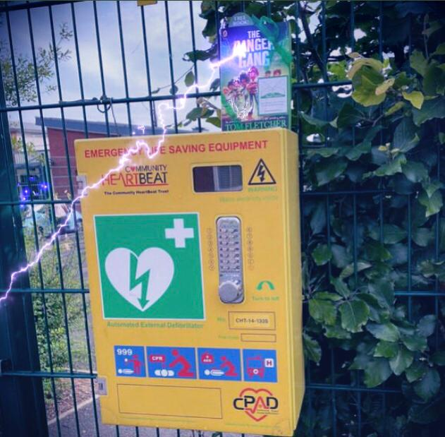 Book Fairies share copies of The Danger Gang by Tom Fletcher at a defibrillator
