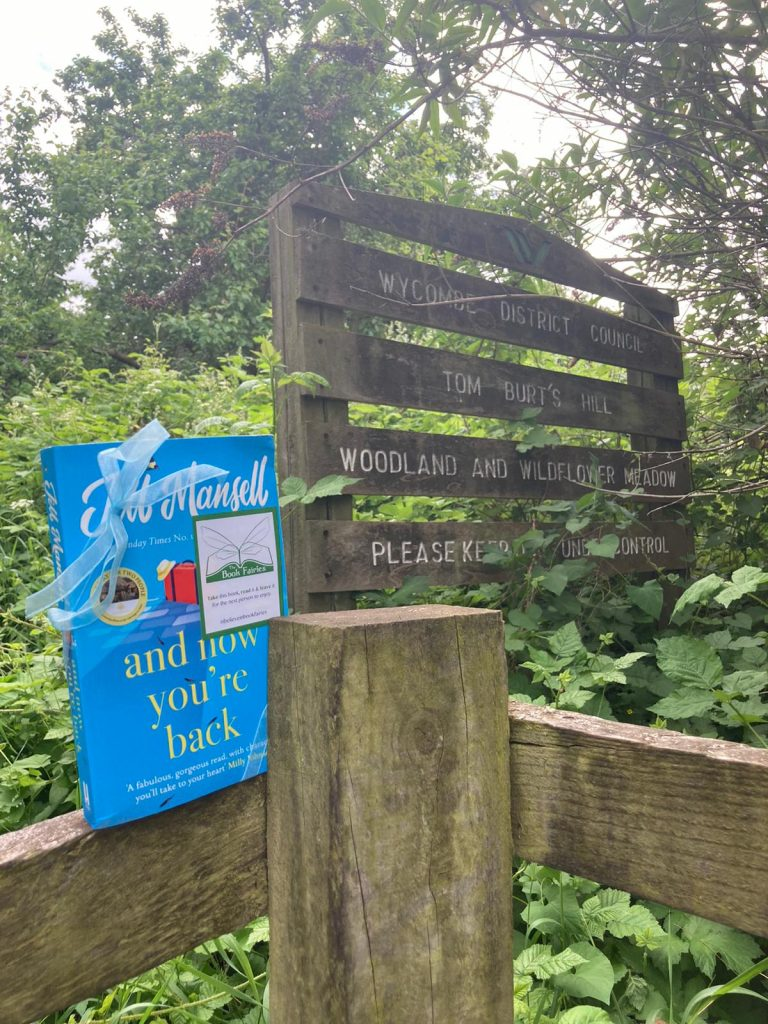 The Book Fairies and Jill Mansell share copies of And Now You're Back on a woodland trail