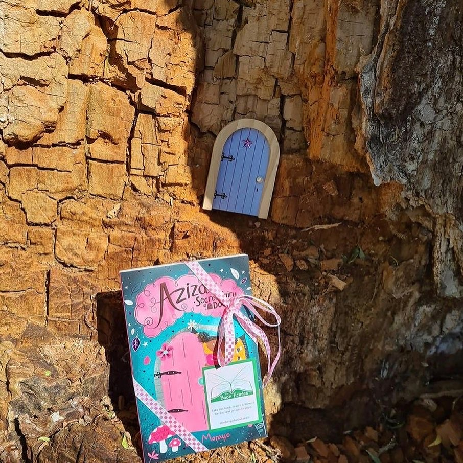 Aziza and the Secret Fairy Door hidden by Book Fairies by a tree