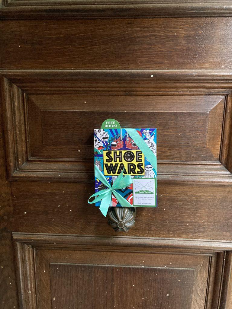 The Book Fairies share Scholastic children's book Shoe Wars at a door