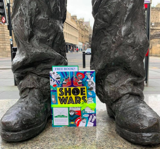 The Book Fairies share copies of Shoe Wars around the UK statue