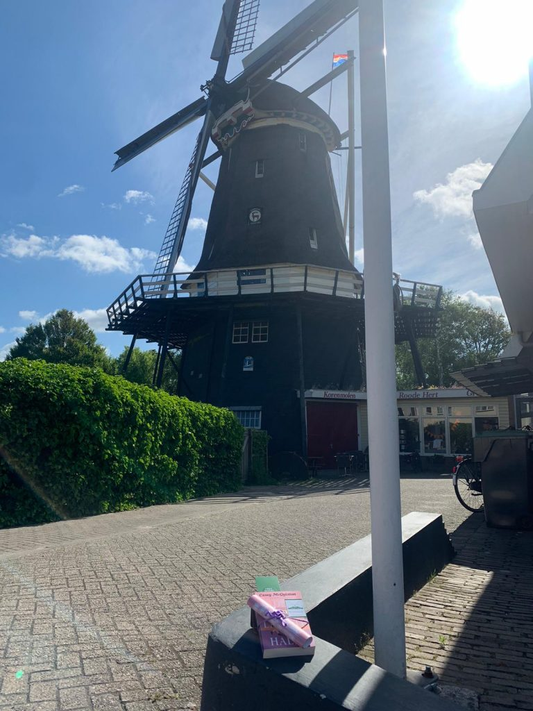 The Book Fairies in the Netherlands shared De Laatste Halte by Casey McQuiston by a Windmill