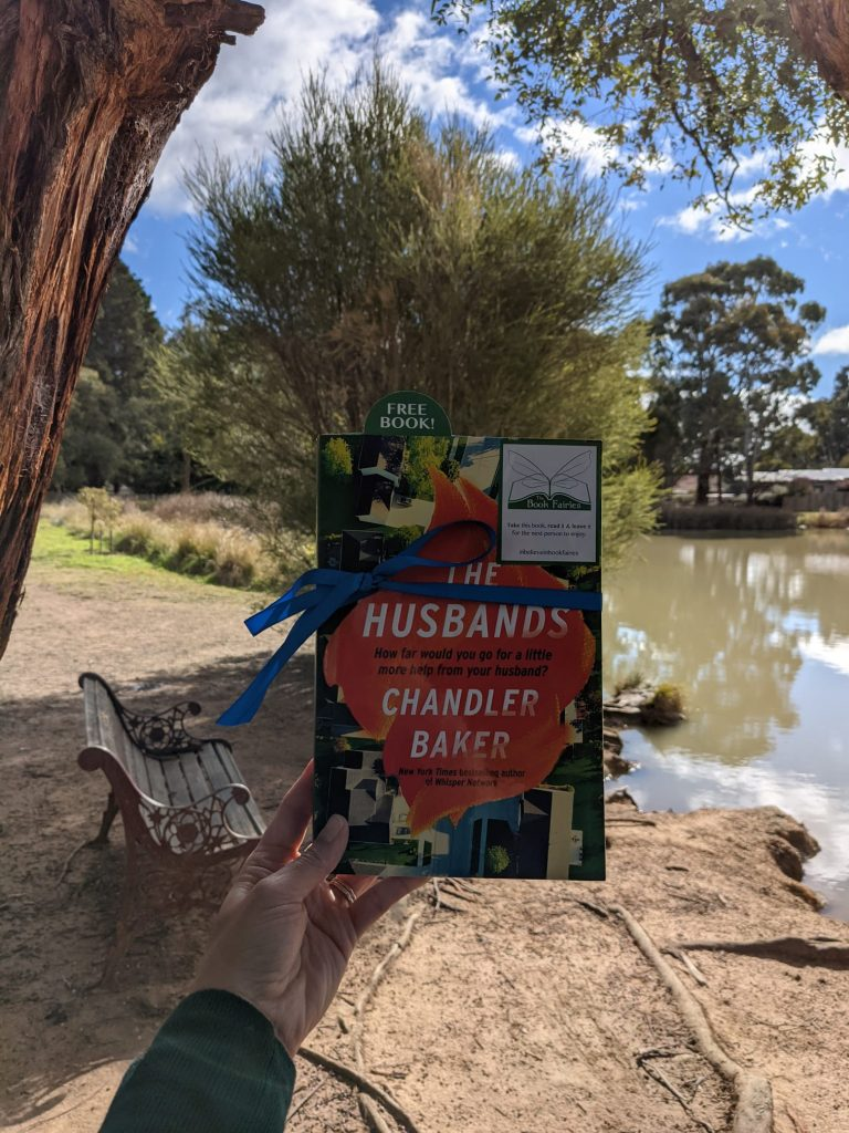 Book Fairies in Australia shared copies of The Husbands by Chandler Baker by a lake