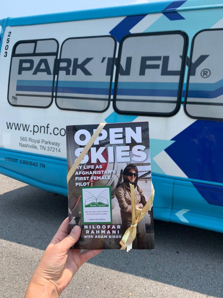 Open Skies by Niloofar Rahmani is hidden by book fairies at a shuttle bus