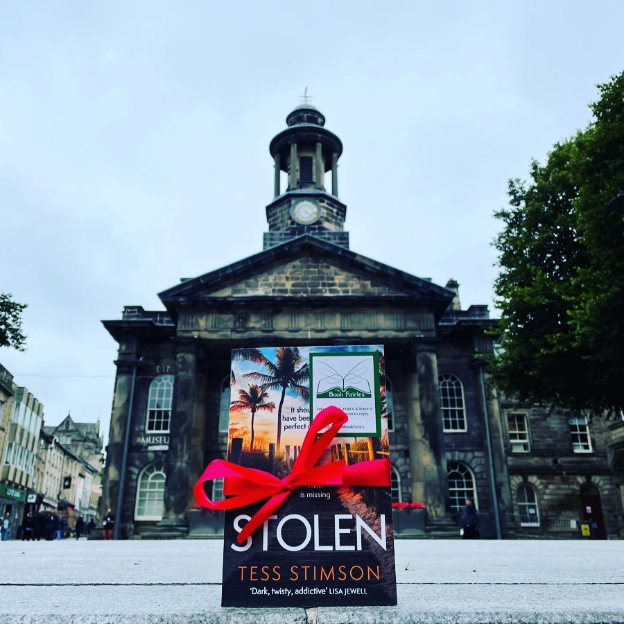 Book Fairies share copies of Stolen by Tess Stimson outside a community hall
