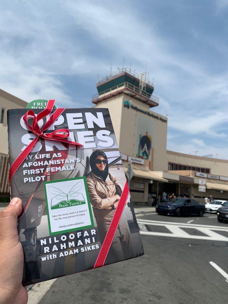 Open Skies by Niloofar Rahmani is hidden by book fairies at an airport