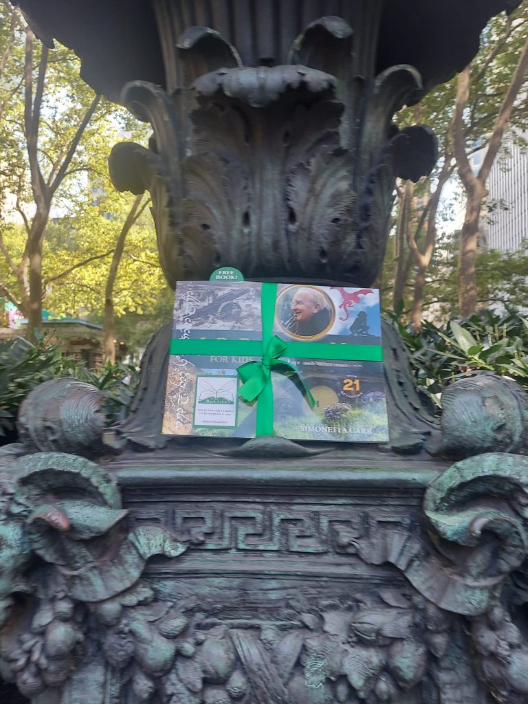 The Book Fairies share copies of J. R. R. Tolkien For Kids at a statue