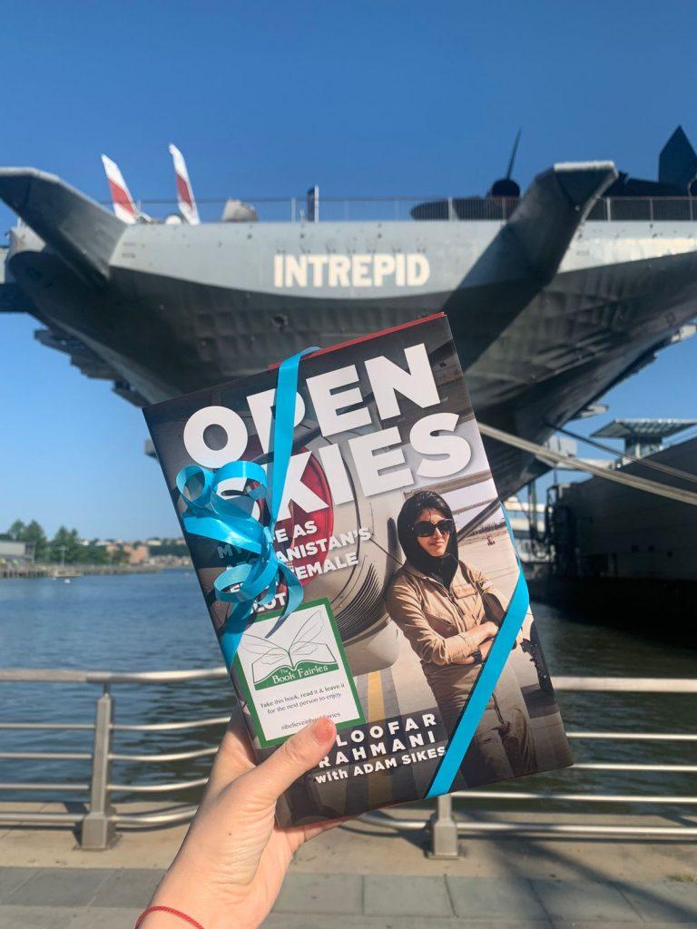 Open Skies by Niloofar Rahmani is hidden by book fairies at an aircraft hanger